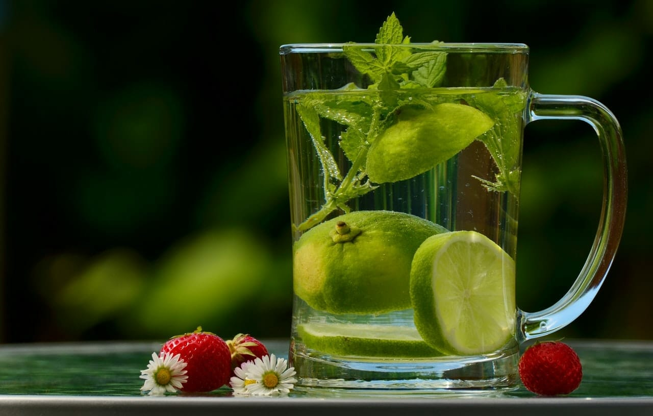 green-round-fruit-on-clear-glass-mug-with-water-122444