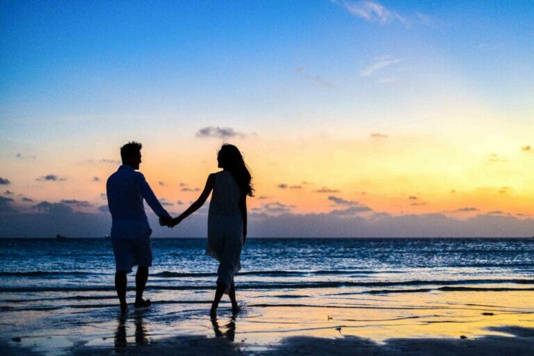 couple walking down beach holding hands