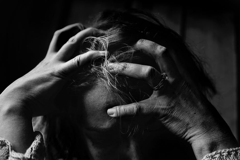 black and white picture of woman grasping hair in frustration