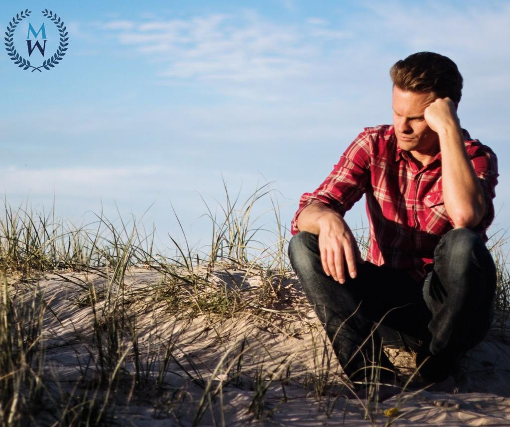 man sitting on sandy hill