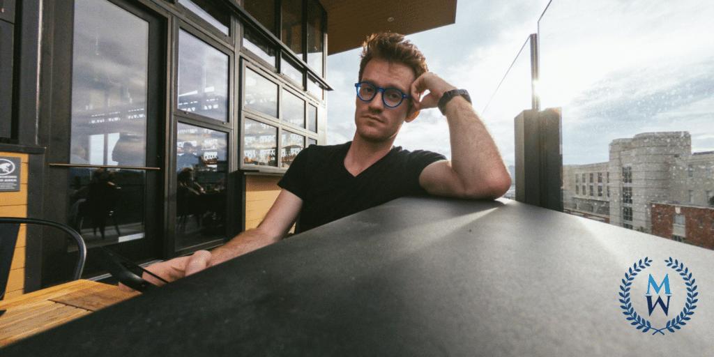 man looking into camera at outdoor rooftop bar