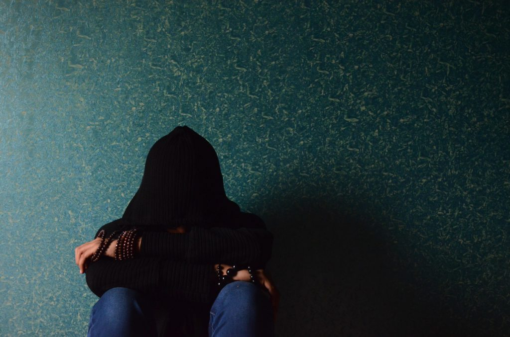person covering face with hood sitting against a wall