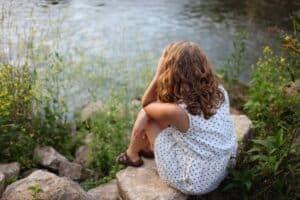girl sitting on rock by lake