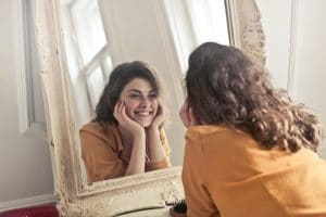 happy woman looking in the mirror