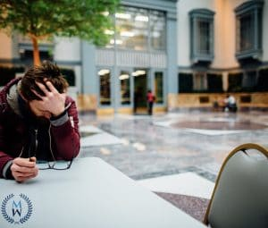 upset man sitting at outdoor plaza table