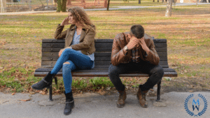 couple upset sitting on park bench