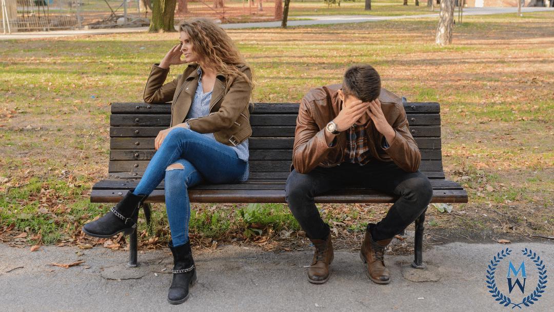 couple upset sitting on park bench