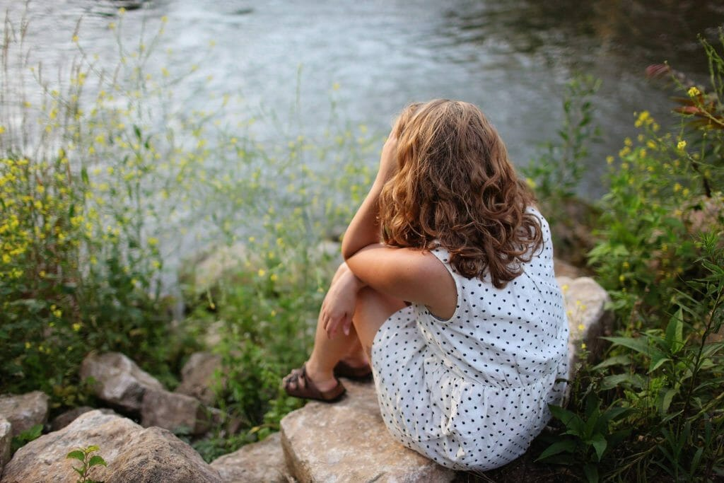 little girl sitting on rock by pond