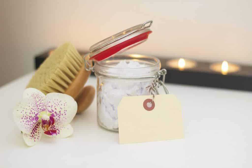 jar of bath essentials next to flower