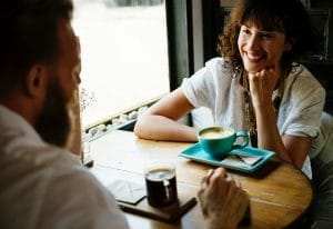 woman happily speaking to man at a table