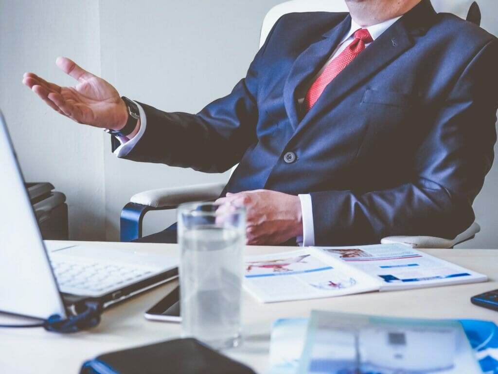 executive sitting at desk making hand gesture