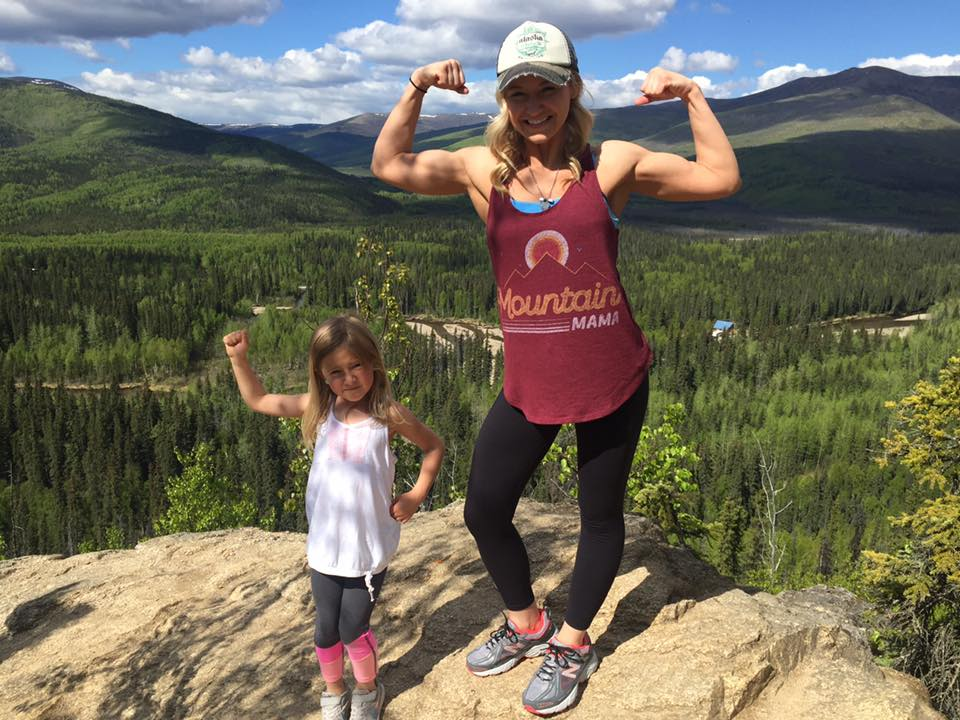 woman and child flexing muscles in the mountains