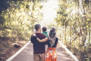 family walking down a wooded road