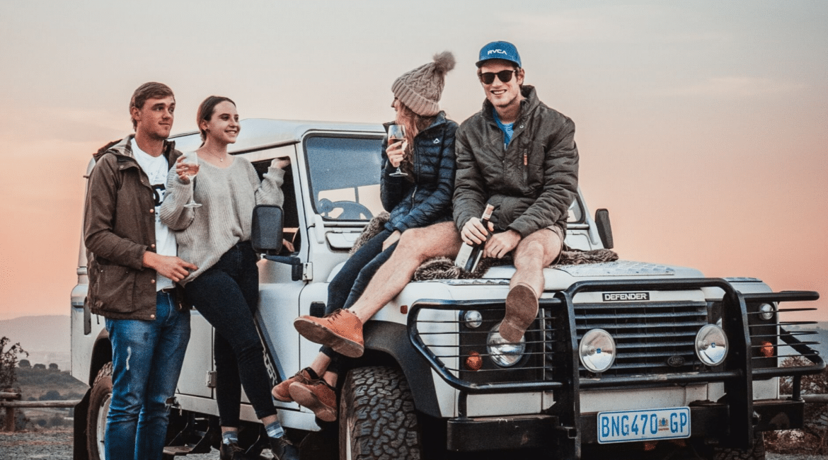 group of friends sitting on a jeep