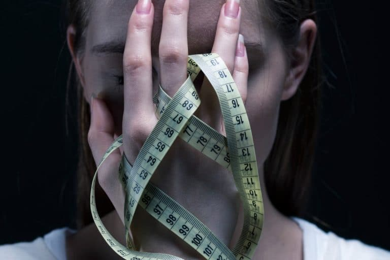 girl holding her face with measuring tape in hand