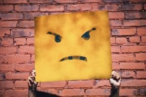 angry face poster being held up