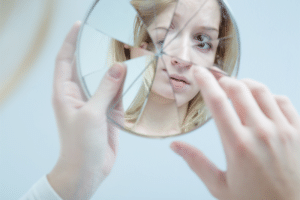 woman touching her reflection in broken mirror