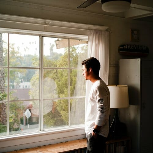guy standing in window looking bored with cabin fever